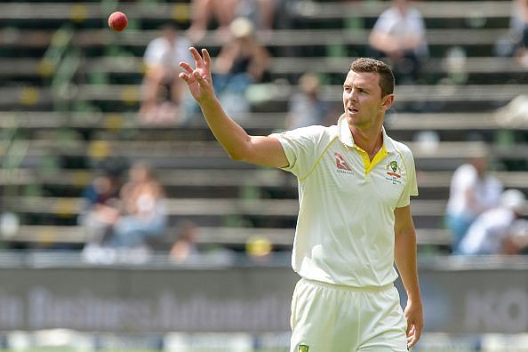 'Josh Hazlewood accepting a ball from his teammate'