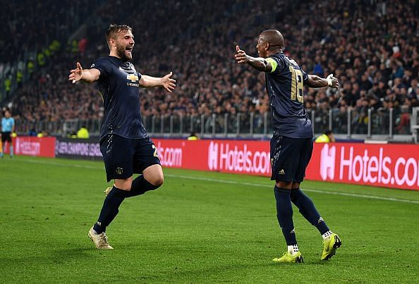 Shaw celebrates one of United's two goals with defensive counterpart Ashley Young in Turin