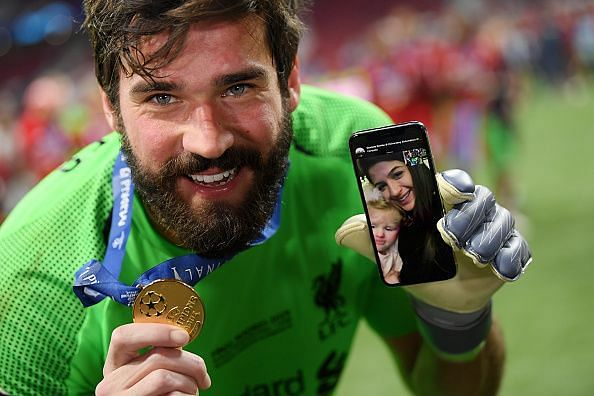 Alisson celebrates with his Champions League winners medal and a video call with family