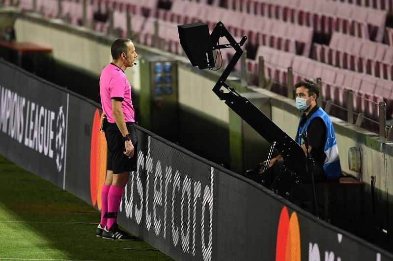 Referee Cuneyt Cakir watches carefully from the pitchside monitor during Barcelona's 3-1 win over Napoli