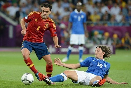 Spain's Xavi Hernandez evades a tackle from Italy's Riccardo Montolivo in Sunday's final