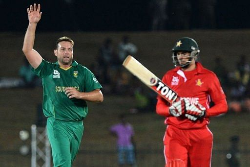 South African cricketer Jacques Kallis (L) celebrates after he dismissed Zimbabwe cricketer Graeme Cremer