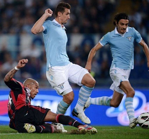 AC Milan's midfielder Nigel de Jong (L) slides to score against Lazio
