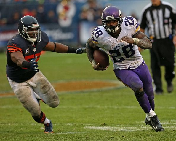 Adrian peterson 28 of the minnesota vikings is chased by lance briggs