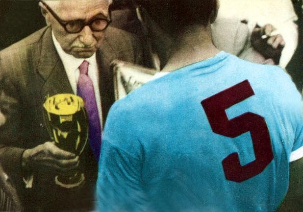 Uruguay's World Cup winning captain Obdulio Varela receives the trophy from Jules Rimet.