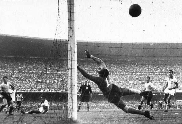 Uruguay's Ghiggia (L) scores the winning goal past the dive of Brazilian goalkeeper Barbosa to win the World Cup for Uruguay and complete a major by upset by beating hosts and favourites Brazil.