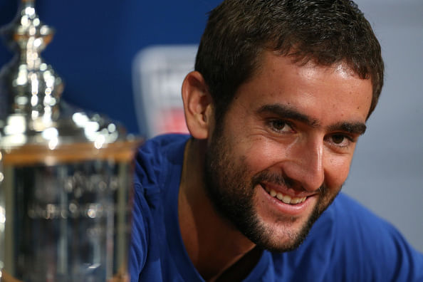 Marin Cilic smiling next to the trophy after winning the 2014 US Open - marin-cilic-us-open-2014-1410272860